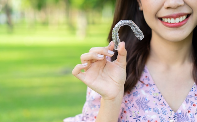 Donna che sorride con la mano che tiene il fermo dentale dell'allineatore (invisibile) al parco naturale all'aperto