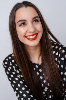 Donna sorridente con un sorriso perfetto e denti bianchi in telecamera. sfondo bianco.