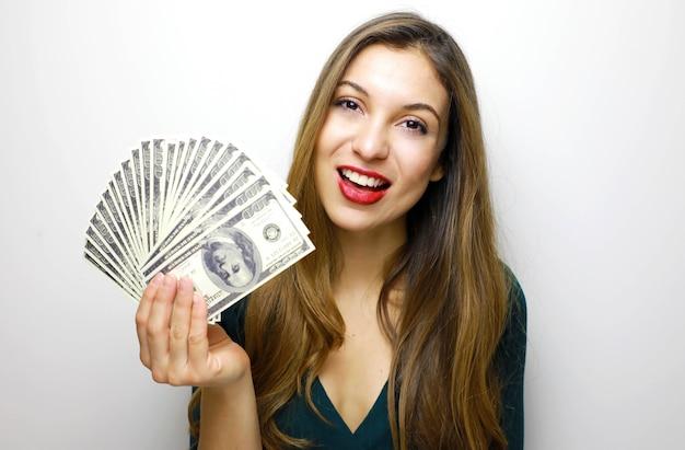Donna che sorride con i denti bianchi e che tiene un sacco di soldi in valuta dollaro