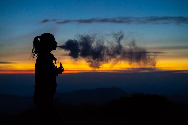 La donna che fuma una sigaretta elettronica sullo sfondo del tramonto