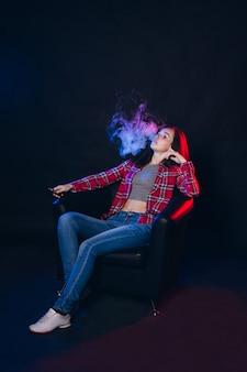 Donna che fuma sigaretta elettronica con fumo