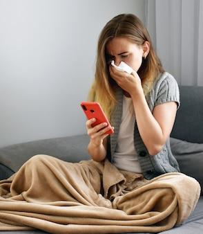 Donna che starnutisce coprendosi la bocca e il naso con un tovagliolo mentre tossisce. freddo, influenza, infezione, virus, covid-19, coronavirus. donna infelice malata sta tenendo il telefono in mano per chiamare il suo medico per il trattamento