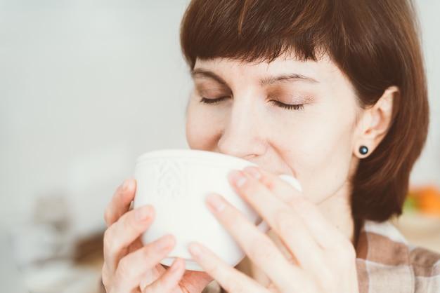 Donna che fiuta odore di caffè dalla tazza.
