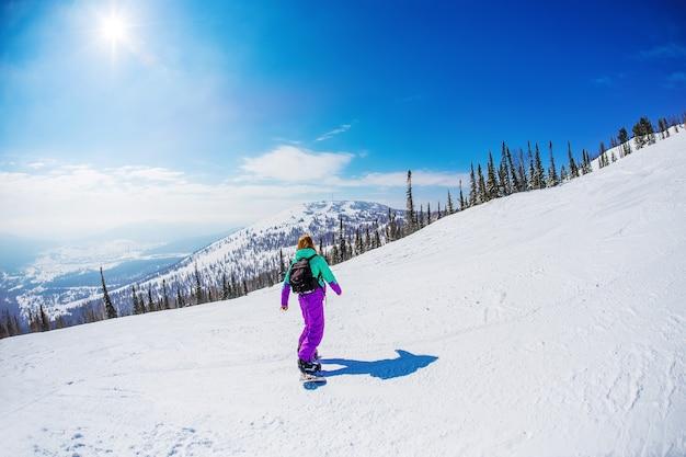 Donna su uno snowboard in montagna sheregesh.