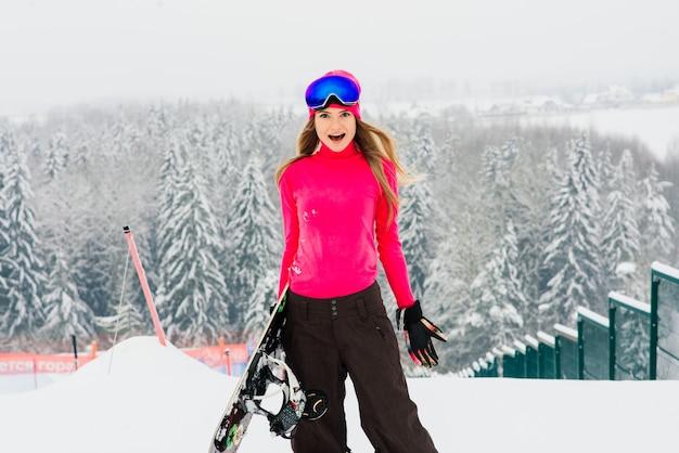 Snowboarder della donna che sta con lo snowboard. ritratto del primo piano della femmina allegra in cima alla pista da sci