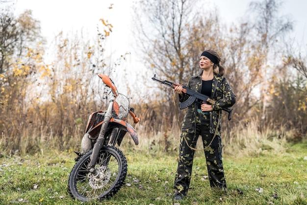 Donna soldato in posa con fucile e moto