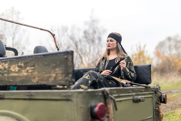 Donna soldato con fucile in posa vicino a un'auto militare