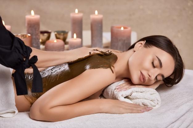 Donna nella spa che riceve un massaggio al cioccolato per la schiena