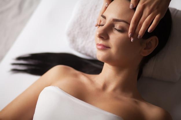 Donna nella spa che riceve il massaggio del viso