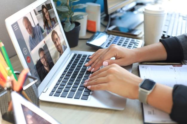La donna parla in videochiamata con i colleghi durante il briefing online durante la quarantena di autoisolamento