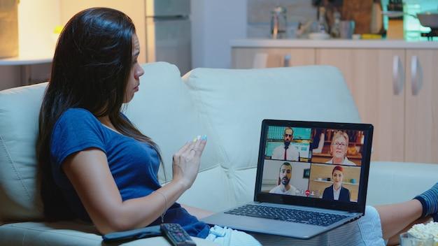 Donna che parla con i colleghi in webcam sdraiata sul divano di casa. lavoratore remoto che ha riunioni online, consulenza in videoconferenza con il team che utilizza la videochiamata che lavora davanti al laptop.