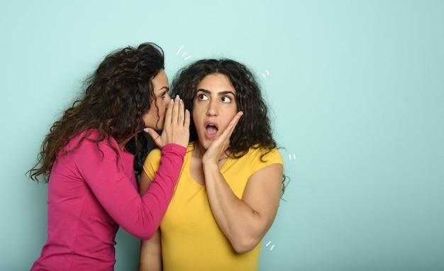 La donna parla nell'orecchio a un amico di una grande promozione. espressione stupita.