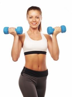 Donna nella pratica dell'attrezzatura sportiva con i pesi della mano, isolati su bianco