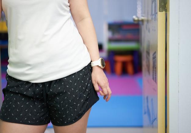 Donna in tuta sportiva posa a casa porta di casa dopo l'esercizio
