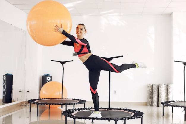 Donna sul trampolino sportivo. allenamento di forma fisica.