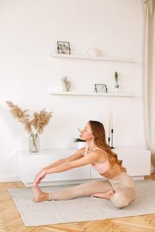 La donna fa sport a casa. yoga