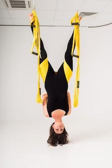 Una donna in tuta sportiva fa esercizi di yoga aereo