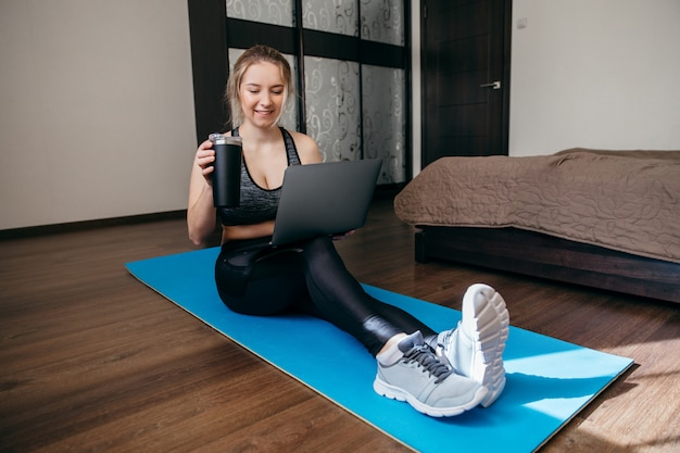 Donna in abiti sportivi che tengono un computer portatile