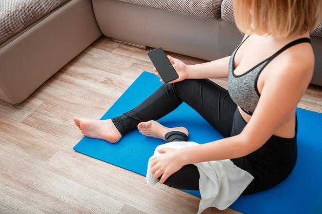 Donna in abbigliamento sportivo che tiene smartphone con schermo vuoto per app per lo sport o la musica durante una pausa di allenamento sul tappetino a casa contro il modello del divano per l'app programma di fitness online lezione di yoga a distanza