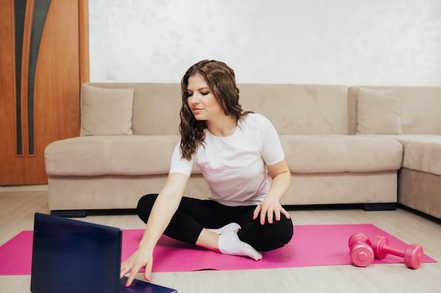 Donna in abbigliamento sportivo è seduta sul materassino yoga rosa con manubri e sta utilizzando un computer portatile