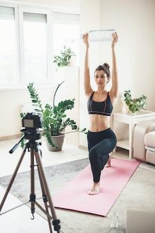 Donna in abbigliamento sportivo si sta allungando davanti alla telecamera utilizzando una bottiglia d'acqua a casa durante le lezioni digitali