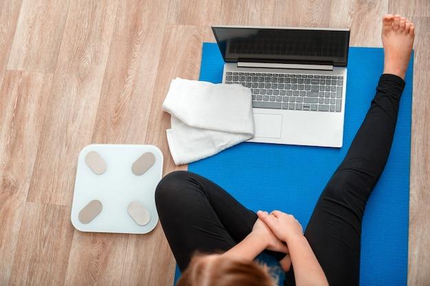 La donna in abiti sportivi fa una lezione di yoga con esercizi di yoga a distanza seduti durante il soggiorno a casa. la giovane donna fa allenamento fitness, esercizi di stretching utilizzando il laptop tramite videochiamata. vista superiore del computer portatile delle scale dell'asciugamano.