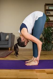 La donna in abiti sportivi esegue esercizi di flessibilità su un tappetino in una stanza