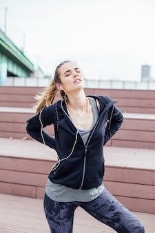Donna in abiti sportivi che soffrono di mal di schiena dopo l'allenamento