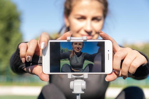 Donna in vlogger di abbigliamento sportivo che si siede sul tappeto erboso artificiale all'aperto