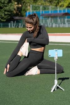 Donna in abbigliamento sportivo vlogger seduto in una posa yoga sul tappeto erboso artificiale all'aperto