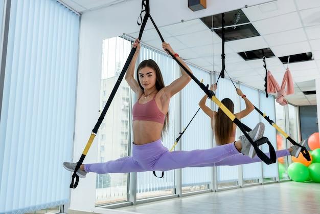 Donna in abbigliamento sportivo che lavora con l'attrezzatura trx e fa esercizio con la gamba in palestra. allenamento femminile per uno stile di vita salutare