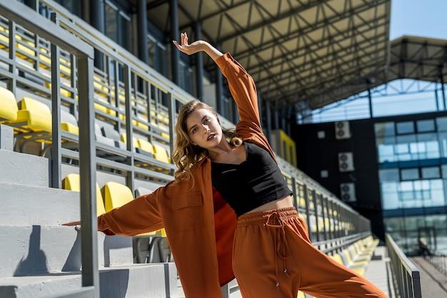 Donna in abbigliamento sportivo che si estende prima del suo allenamento nello stadio. stile di vita