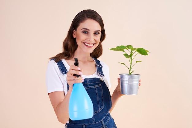 Donna che spruzza le piante con spray per insetti