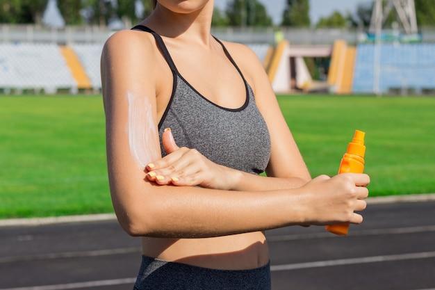 Crema solare di spruzzatura della donna sulla pelle prima dell'esecuzione. sport e concetto sano