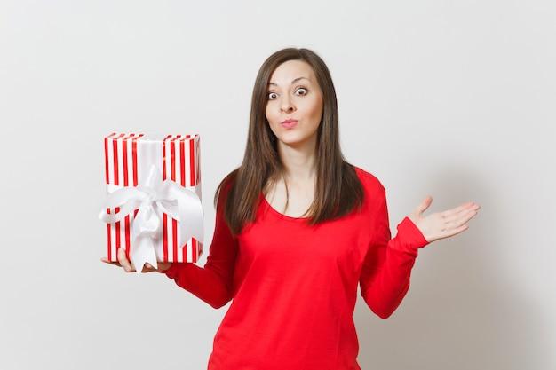 Donna allargando le mani, tenendo la scatola presente a strisce rosse con nastro isolato su sfondo bianco. per la pubblicità. san valentino, giornata internazionale della donna, natale, compleanno, concetto di vacanza