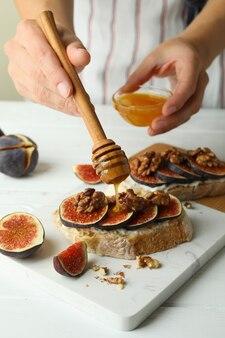 La donna spalma il miele sulla bruschetta con il fico