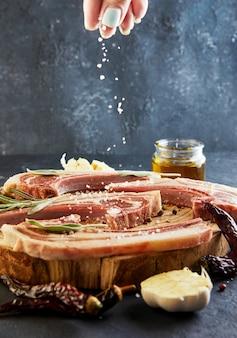 Una donna cosparge di sale su un raw lamb ribs con gli ingredienti per cucinare