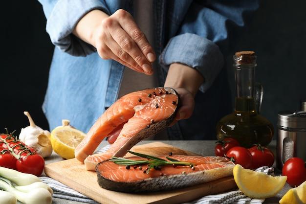 La donna spruzza il sale sulla carne di color salmone
