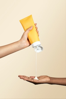 Donna che spreme la crema da un tubo giallo senza etichetta