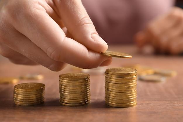 Donna che impila le monete sulla tavola di legno, primo piano