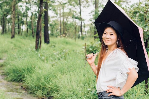 La donna sta e sorride tiene un ombrello nella foresta pluviale