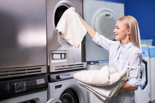 Donna in piedi da sola con vestiti puliti nella lavanderia self-service con asciugatrici. femmina in abbigliamento casual sta tenendo il bacino con i vestiti, felice dopo aver ricevuto asciugamani puliti
