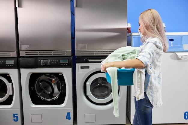 Donna in piedi da sola con vestiti sporchi nella lavanderia self-service con asciugatrici. femmina in abbigliamento casual sta tenendo il bacino con i vestiti.