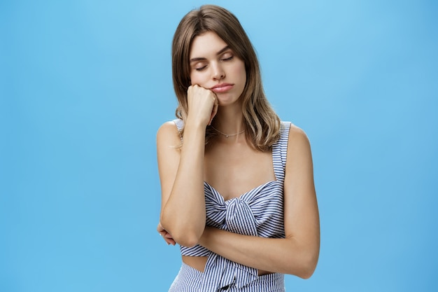 Donna in piedi annoiata e assonnata che fa un pisolino mentre ascolta i discorsi noiosi del capo appoggiato la testa sul pugno chiudendo gli occhi e dormendo stanco e indifferente sul muro blu con espressione rilassata.