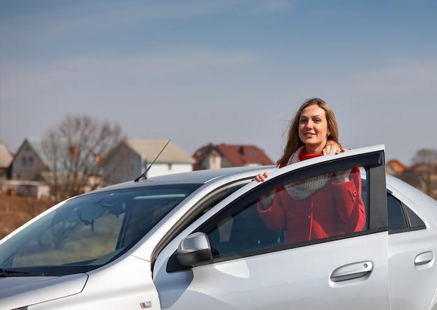 Donna in piedi in macchina su uno sfondo di case
