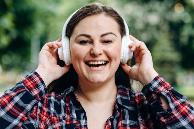 Donna in piedi in città e ascoltando la canzone preferita in cuffia. il ritratto all'aperto della ragazza europea vaga indossa le cuffie bianche.