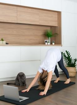Donna in piedi in una posa di cane rivolto verso il basso mentre si fa yoga online a casa. il suo gatto la sta guardando.