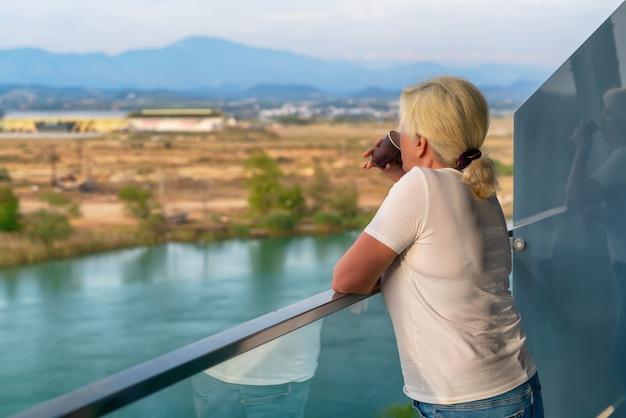 Donna in piedi su un balcone esterno rialzato