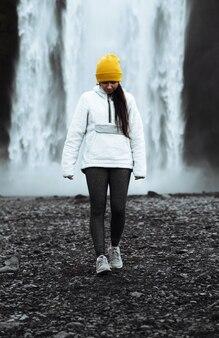 Donna in piedi di fronte alla cascata skógafoss, islanda