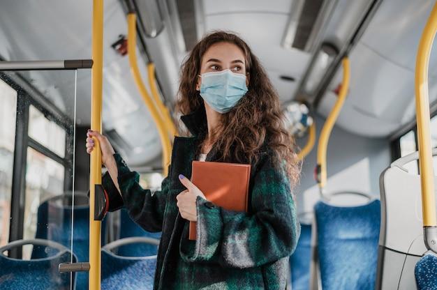 Donna in piedi e tenendo il palo dell'autobus